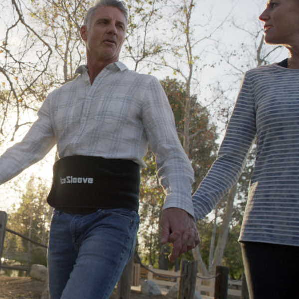 man walking in park wearing lower back icesleeve